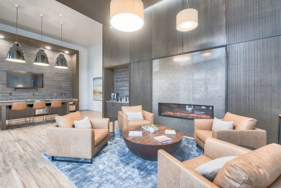 Resident seating near fireplace in clubhouse at Tera Apartments, WA, 98033
