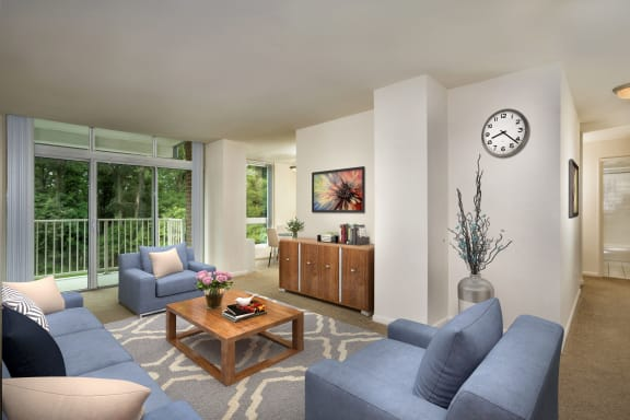 furnished living room at Charlestowne North apartments in Greenbelt with blue couch and chairs, coffee table,  wall clock, wall mounted TV and wood cabinet