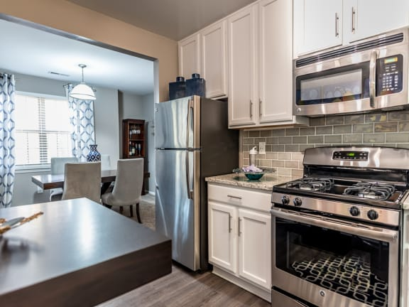 Versailles Towson apartments kitchen with stainless steel appliances and white cabinets
