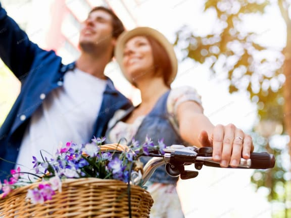Women and man taking photo while holding a bike handle.