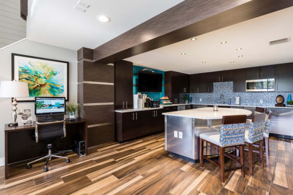 Club house kitchen with center island, bar stools and wood style flooring.