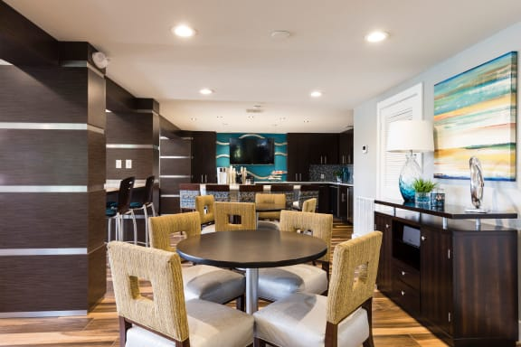 Club house kitchen area with round tables and chairs.