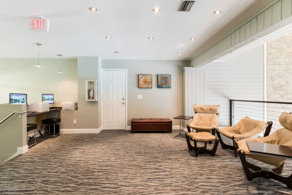 Setting area in club house with lounge arm chairs and carpeted floors.