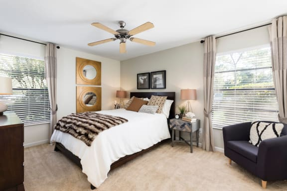 Bedroom with carpet, drapery, bed, nightstand, arm chair and ceiling fan.