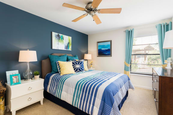 Bedroom with two nightstands, bed and ceiling fan.
