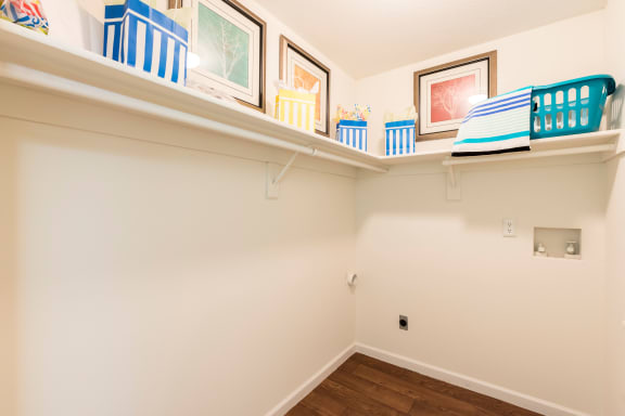 Laundry room with wood style floors and shelves.