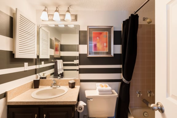 Bathroom with dark brown cabinets, white toilet, white sink and tan tile shower surround.