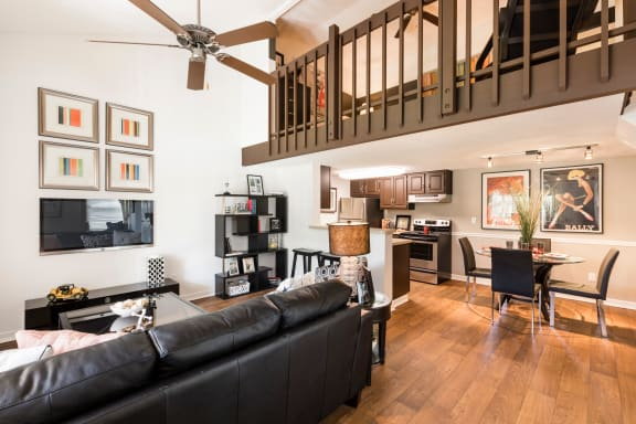 Living room with dark black couch, wood style floors, ceiling fan and brown loft banister.