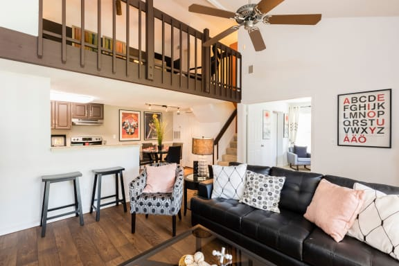 Living room with black couch, coffee table, bar stools, loft railing and ceiling fan.