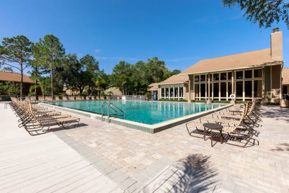 Pool deck with lounge chairs, and clubhouse with trees in the background.
