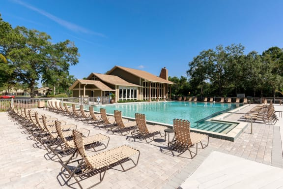 Two rows of lounge chairs, pool, tress and the club house in the background.