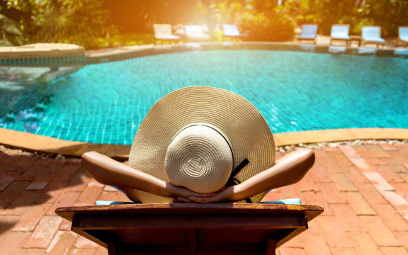Women relaxing by pool with hands crossed behind her head while wearing a floppy hat on her head.