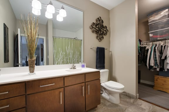 Be @ The Calhoun Greenway Apartment Bathroom with Sink, Toilet, White Counters, and partial Walk-In Closet
