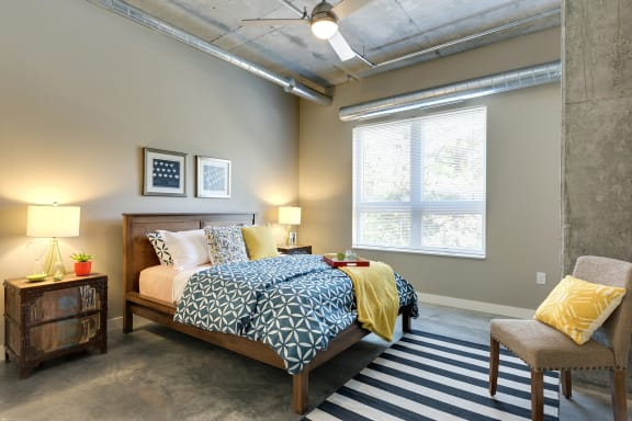 Be @ The Calhoun Greenway Apartment Bedroom with Large Window and Concrete Floor