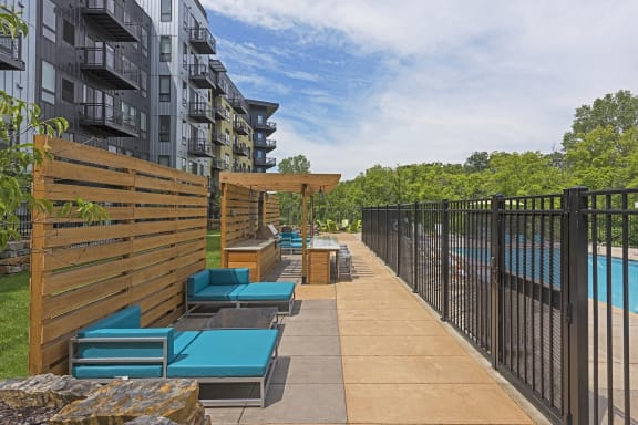 Be @ The Calhoun Greenway Poolside Lounge Area with blue couches and grill area