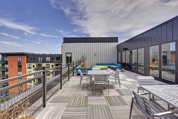 Be @ The Calhoun Greenway Rooftop Patio with tables, chairs, and couches