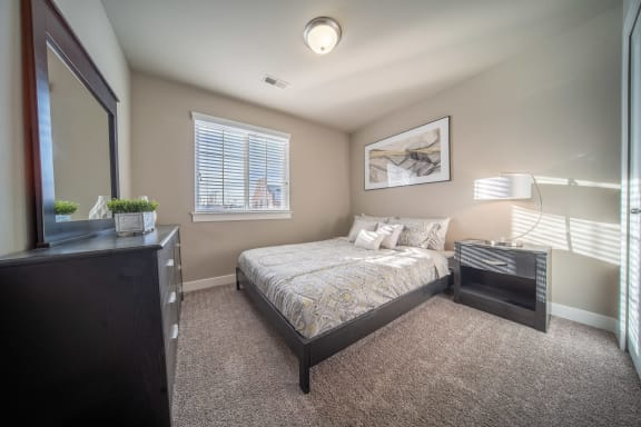 Bedroom with plush carpeting and wall decor