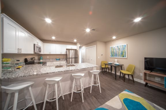 Kitchen island with white barstools with bartop table and TV
