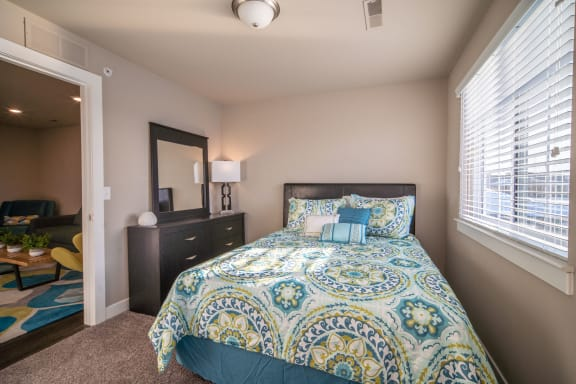 Bedroom with bed, plush carpeting, and dresser with mirror