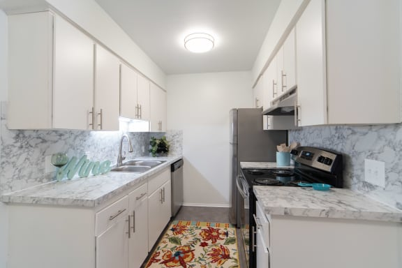 Kitchen with marble like countertops, white cabinets, and stainless steal appliances.