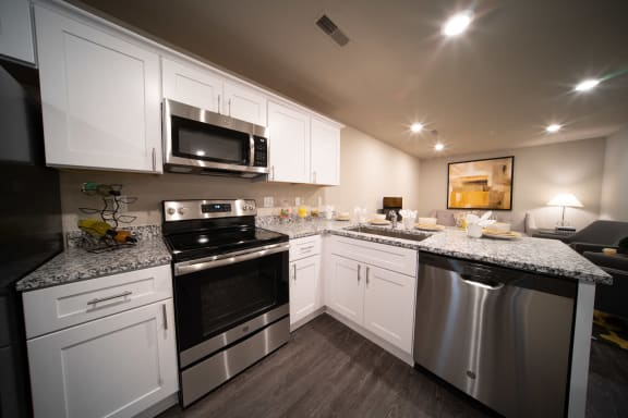 Kitchen with white cabinets, granite counters and stainless appliances