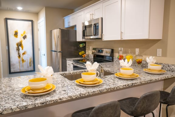 Kitchen with granite counters, stainless appliances and seating area