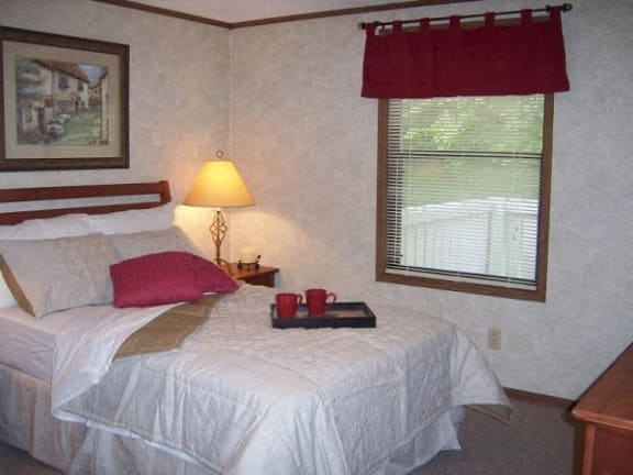 Furnished bedroom with red accent pillows and curtains