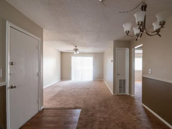 Living and dinning area with plush carpeting, and light neutral walls and a silver chandler.
