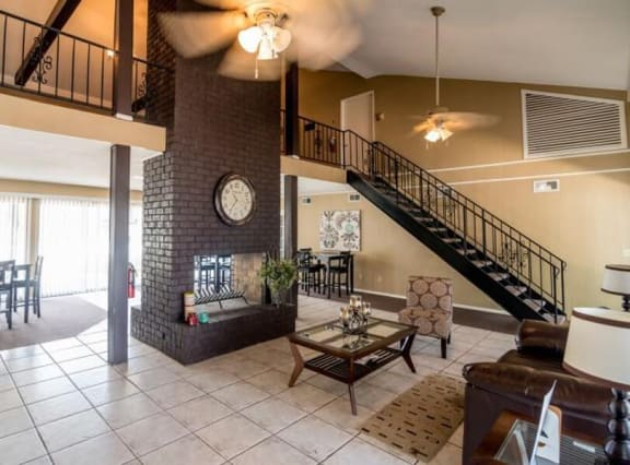 Clubhouse at Atwood Oaks. Large open room with tile floor and a large brown fireplace.