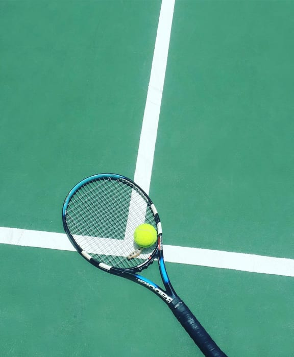 Green and white tennis court with a tennis racket and tennis ball laying on it.