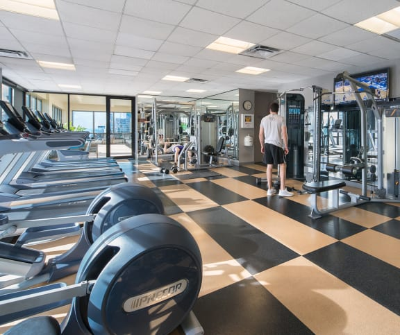 Fitness center with cardio and weight training machines with main standing near mirrors