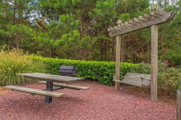wooden bench swing near picnic table and grill