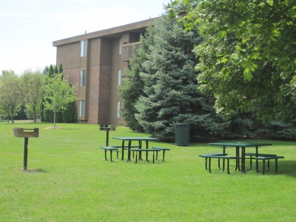 Outdoor Picnic and BBQ Areas with beautiful green landscaping at Dover Hills Apartments at 4520 Dover Hills Drive, Michigan