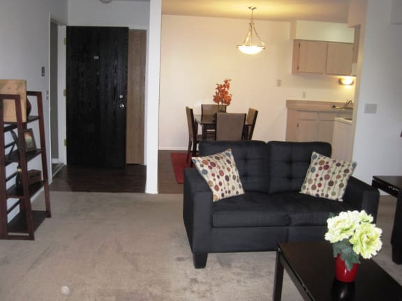 Living room with couches and dining area in Short-Term Furnished Units Available at Dover Hills Apartments, Michigan
