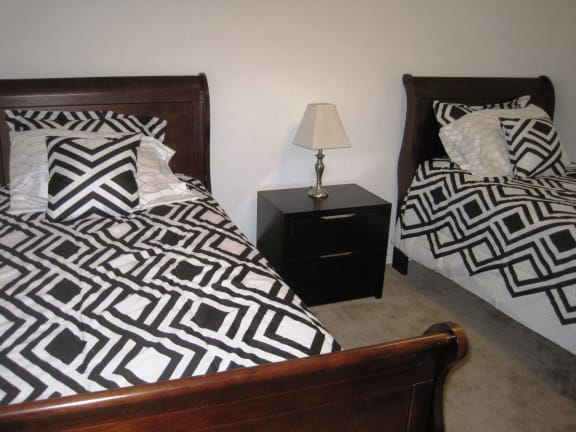 Bedroom with twin beds in Short-Term Furnished Unit available at Dover Hills Apartments in Kalamazoo, Michigan
