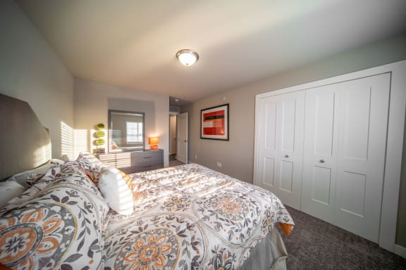 Bedroom with plush carpeting and closet