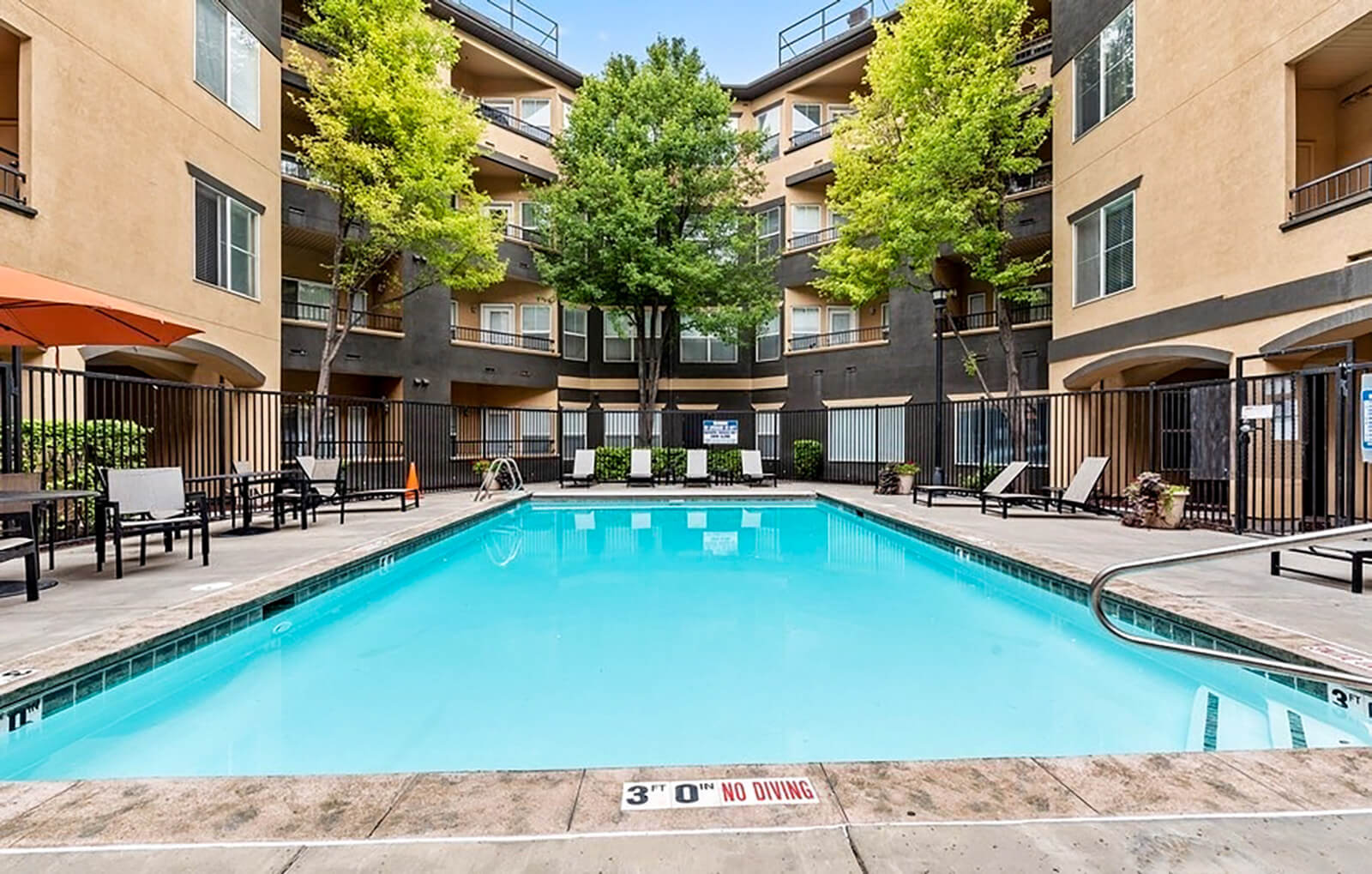 Long rectangular apartment pool with apartment building in the background
