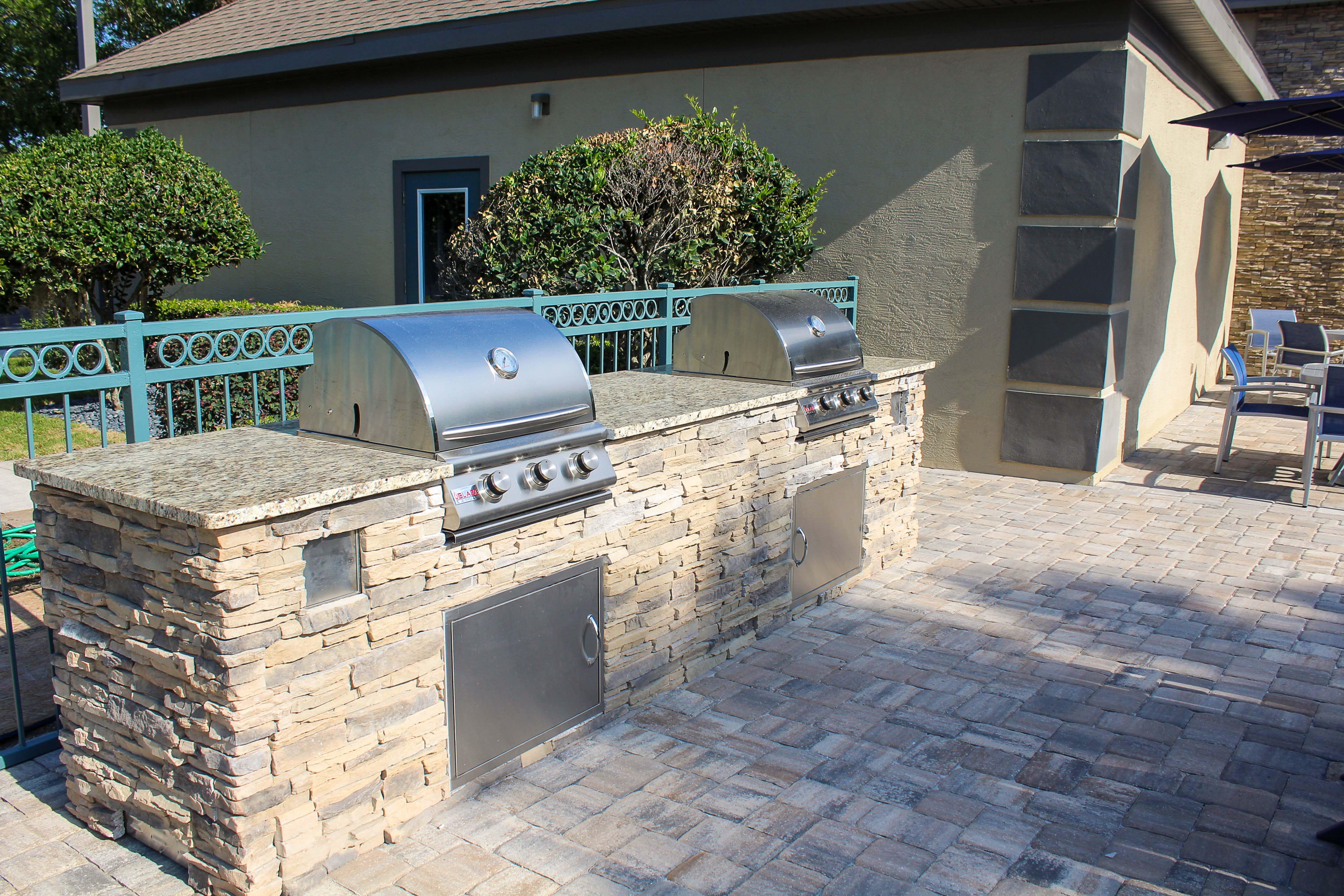 Outdoor kitchen with gas grills pool-side