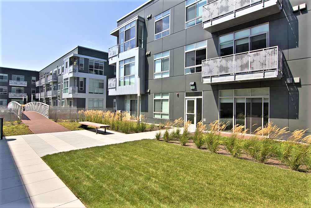 Exterior image of DuCharme Place. Grey sidewalk and green grass area with grey building in back.