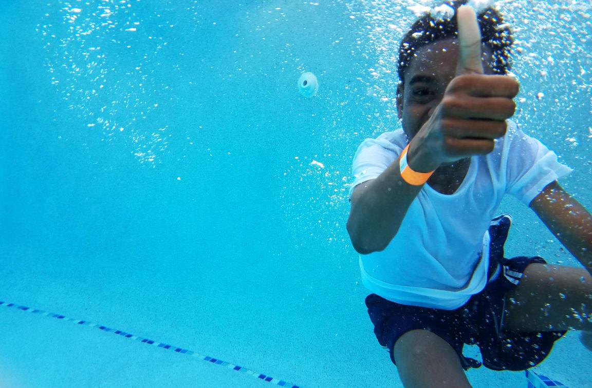 kid swimming in sparkling pool at Preserve at Melrose Vista, CA