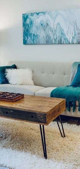 White couch with throw pillows and blanket. Blue artwork above couch. Coffee table in front of couch