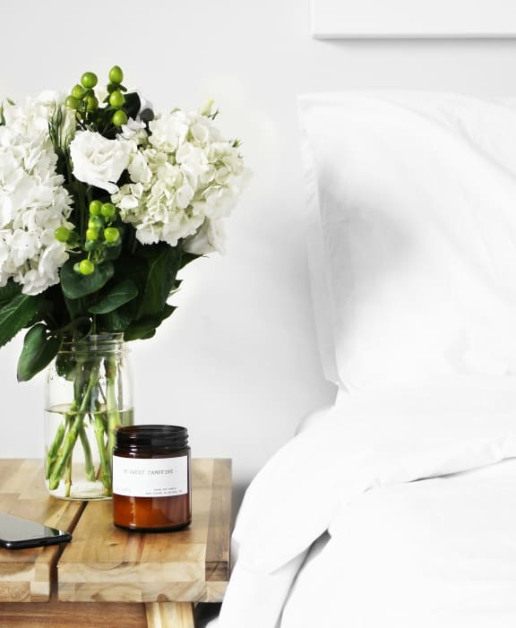 White bed with wooden nightsand with flowers and candle