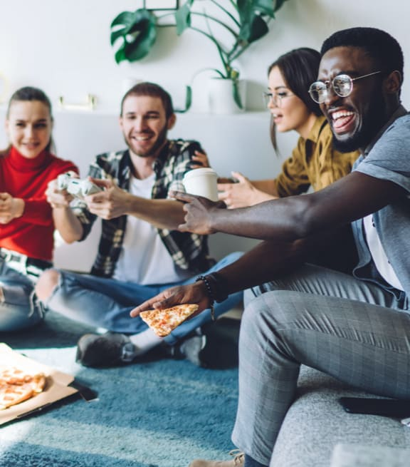 Friends enjoying pizza, coffee, and video games