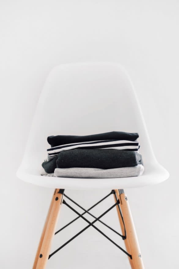 Laundry folded on chair against wall
