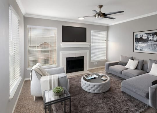 Model living room carpet and 3 large windows with TV above fireplace in middle.