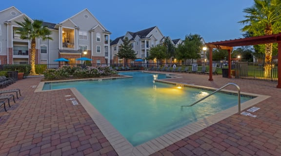 Pool view with side lounge chairs, pergola and apartments in the background at dusk