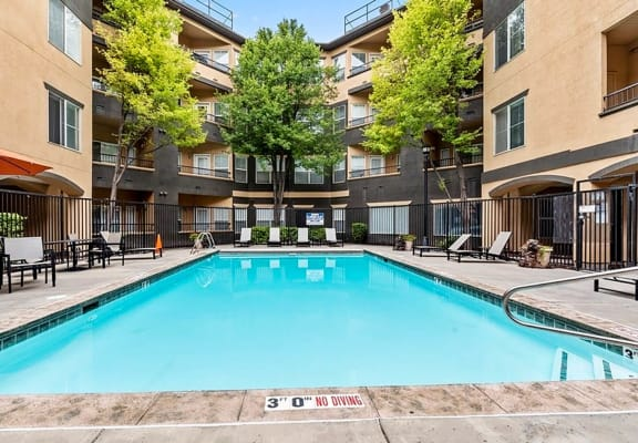 Long rectangular apartment pool with apartment building in the background.