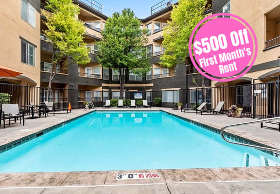 Long rectangular apartment pool with apartment building in the background. $500 off first month rent text