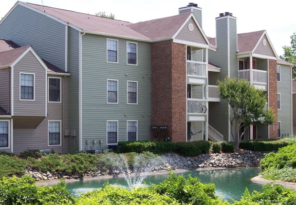 Apartment building exterior with pond and fountain at Park 2300 apartments in Charlotte, NC
