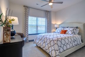 master bedroom with window and high vaulted ceilings